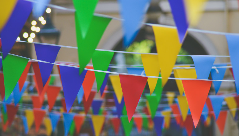 Red, blue, yellow, and green triangle banners on strings draped across a street to celebrate a fiesta