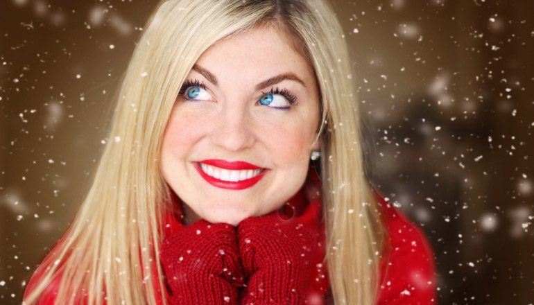 blond girl with a big toothy smile, red lipstick, gloves and sweater with light snow falling