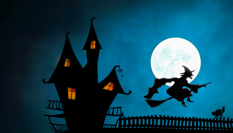 Witch flying in front of the moon next to a haunted house