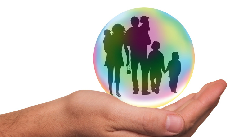 open hand holding a globe containing a small family