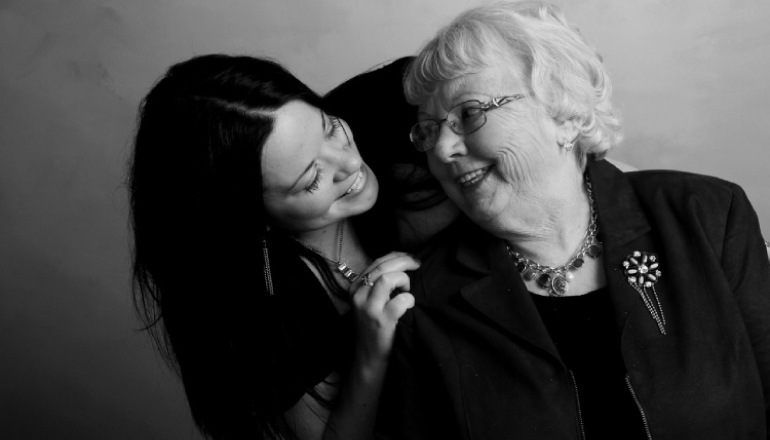 granddaughter leans over to embrace and smile at her grandmother
