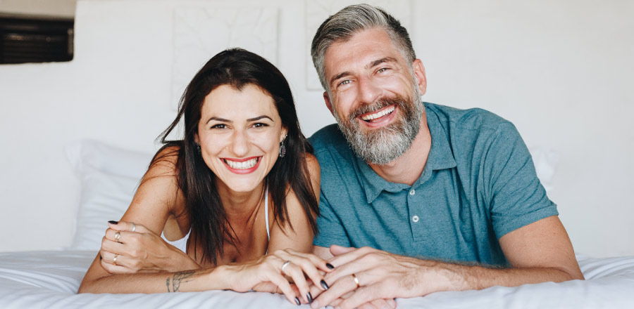 A husband and wife with healthy gums smile in Katy, TX